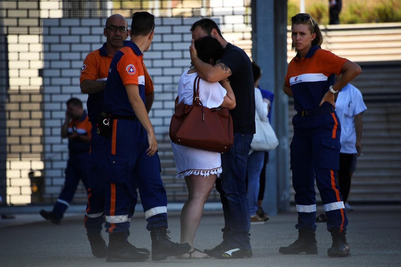 Des agents de la protection civile réconfortent une femme devant l'hôpital Pasteur de Nice, le 17 juillet 2016   / AFP