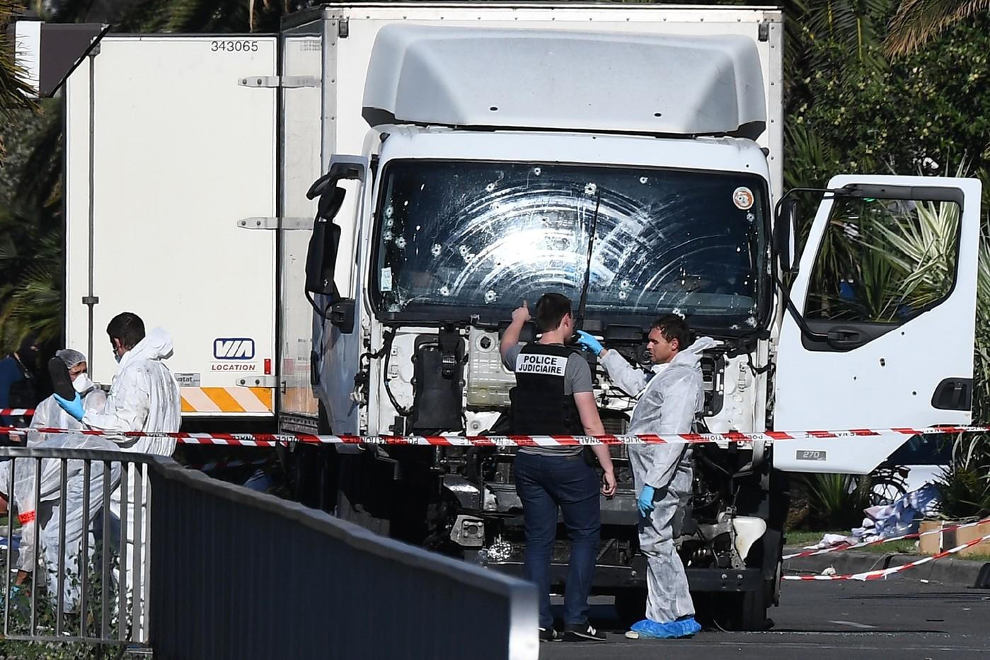 Des experts scientifiques de la police devant le camion criblé de balles de l'auteur de l'attentat sanglant de Nice, le 15 juillet 2016 / AFP