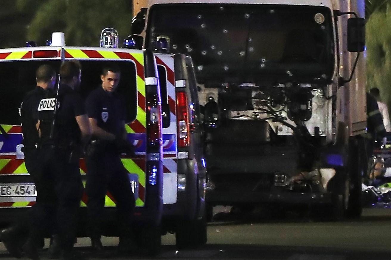 Des policiers se tiennent, le 17 juillet 2016, près du camion précipité sur la foule le soir du 14 juillet à Nice  / AFP