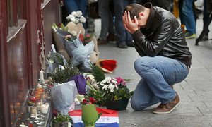 A man pays his respect outside the Le Carillon restaurant the morning after the attacks in Paris in November.