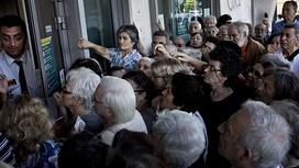 The manager of a national Bank branch delivers priority numbers to pensioners, as Greece reopened banks for pensioners who do not use cash cards for ATM, to allow them to withdraw their pension with a limit of 120 euros, in Athens on July 1, 2015. The European Union will decide whether to grant Greece a last-minute bailout package to avoid pushing it further towards an exit from the eurozone. Greece failed on the eve to make a 1.5 billion euro (1.7 billion USD) payment to the International Monetary Fund, becoming the first industrialised country to do so. AFP PHOTO / ANGELOS TZORTZINISANGELOS TZORTZINIS/AFP/Getty Images