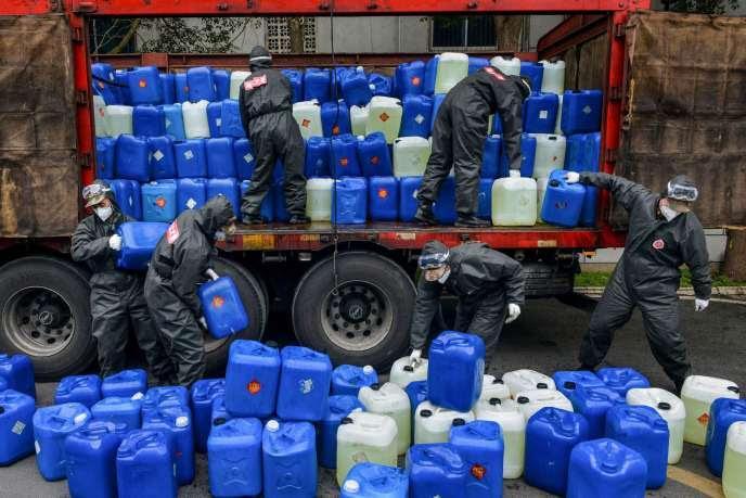 Des policiers chinois déchargent du désinfectant à               Xiaogan, dans le Hubei, le 12 février.