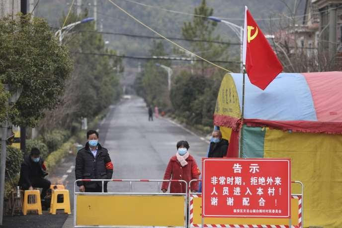 Des volontaires sur un barrage routier dans le               village de Hangzhou, dans la province du Zhejiang, àl'est               de la Chine, lundi 3 février.