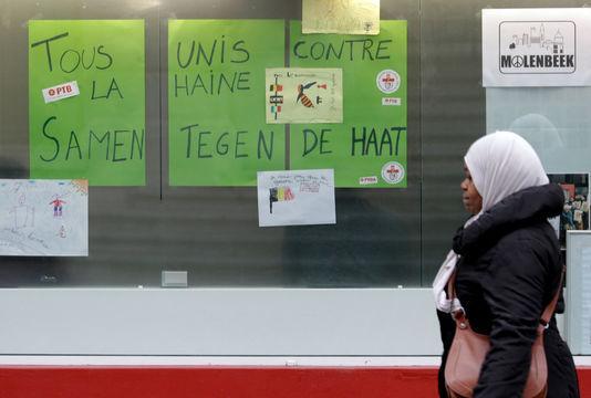 """Une femme du quartier marche devant des pancartes """"Nous sommes tous unis contre la terreur"""", le 20 novembre 2015."""