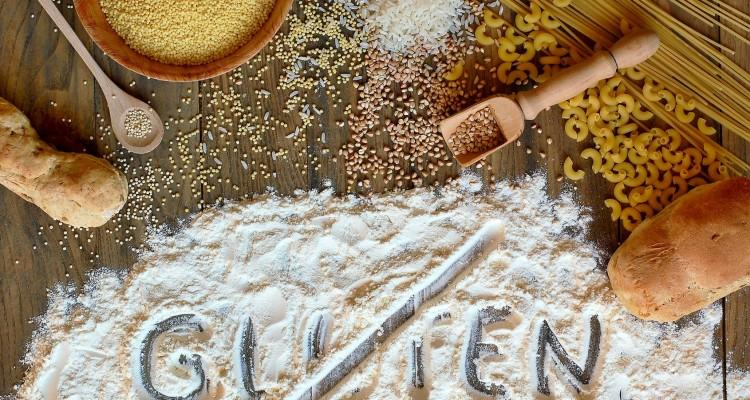 Gluten free cereals corn, rice, buckwheat, quinoa, millet, pasta and flour with scratched text gluten on brown wooden background,overhead horizontal view