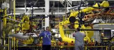 Auto workers feed aluminum panels to robots at Ford's Kansas City Assembly Plant where new aluminum intensive Ford F-Series pickups are built in Claycomo, Missouri May 5, 2015. REUTERS/Dave Kaup - RTX1BPMS