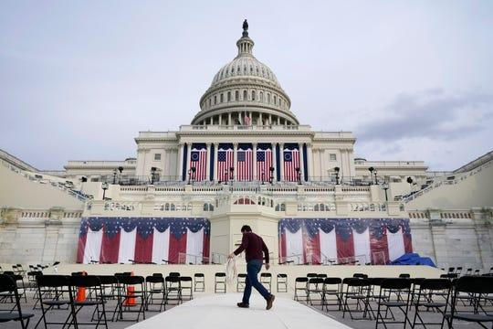 A worker pulls cables as preparations take place for President-elect Joe Biden's inauguration ceremony at the U.S. Capitol in Washington, Jan. 16, 2021.