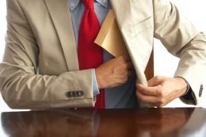 封筒を内ポケットに入れる男性