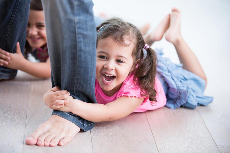 bigstock-Playful-girls-holding-father-s-92245946.jpg