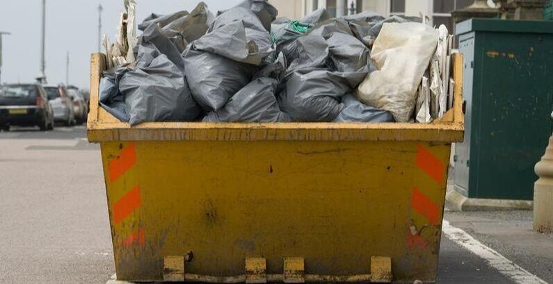 garbagecontainerfilledwithtrashbagsinacityv2.jpg