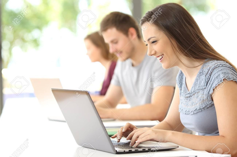84001752-side-view-of-a-happy-student-searching-on-line-with-a-laptop-at-classroom.jpg